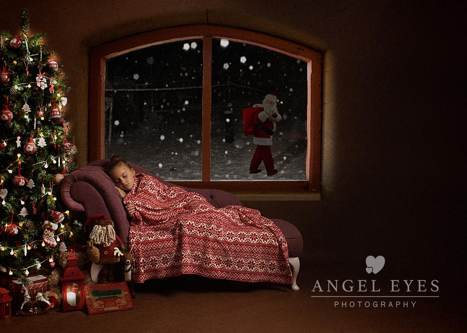 Girl lying down with santa in window