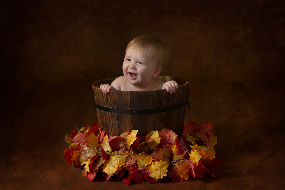 baby in bucket with autumn leaves - baby photographer taunton