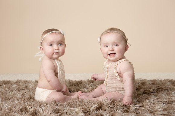 Twins sitting facing each other baby photographer taunton