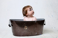 Baby in the bath with bubbles - photographer somerset